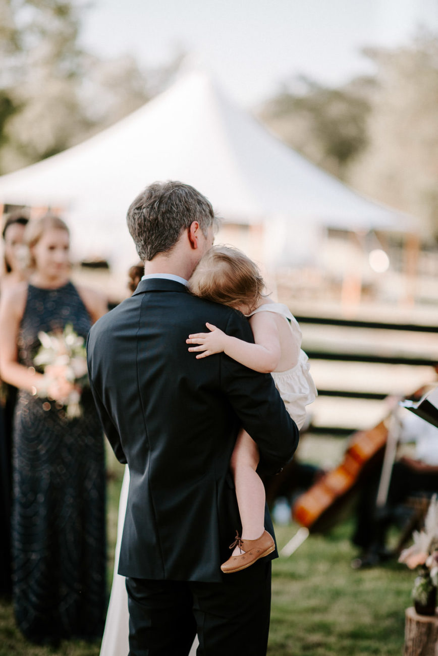 Groom holding daughter at alter