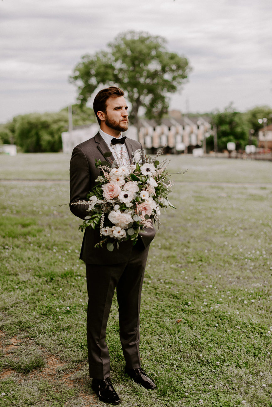 stylish groom holding bouquet downtown Nashville